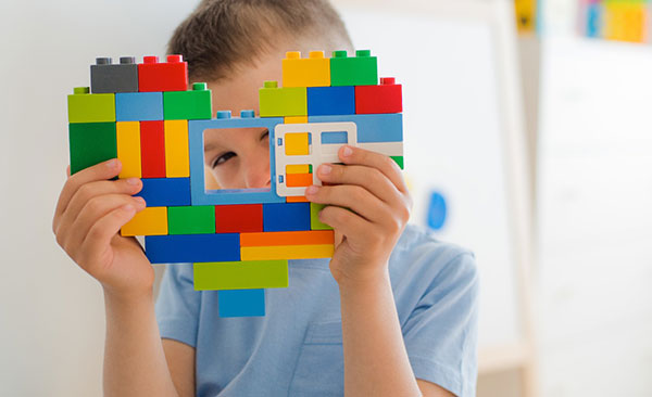 Young boy looking through lego blocks