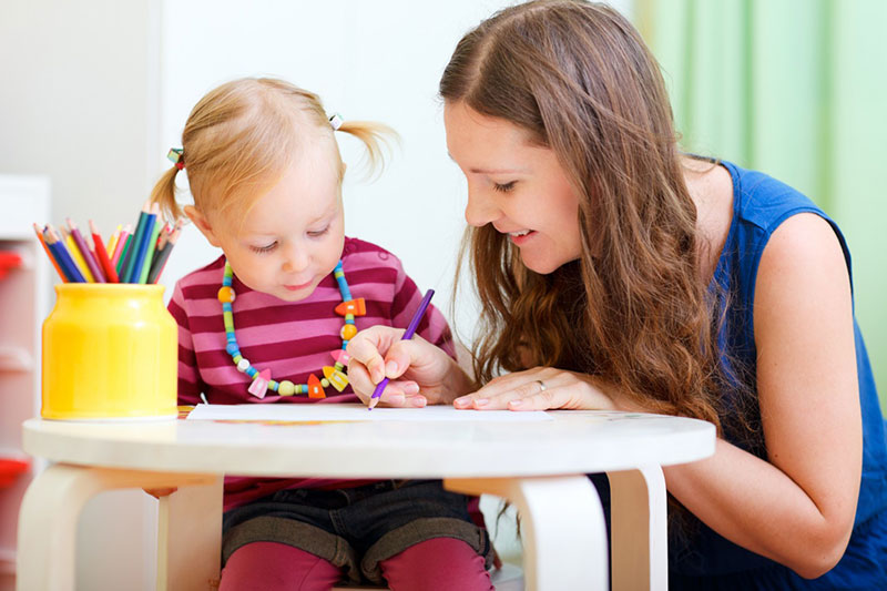 Young person helping toddler colour