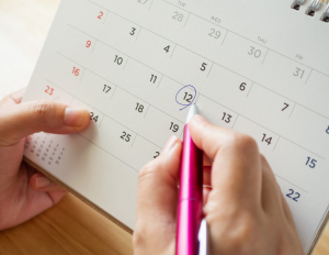 A calendar of the month with a person circling a date.