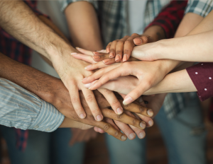 A group of people putting their hands together.
